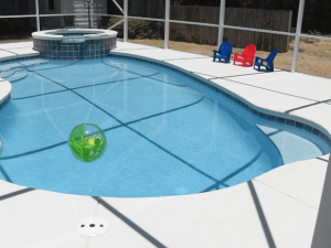 Enclosed pool and spa combination with concrete deck coating in silver.