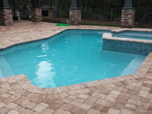 Pool-Spa combination with cove blue plaster, mojave aqua tile, and sandstone colored coping.